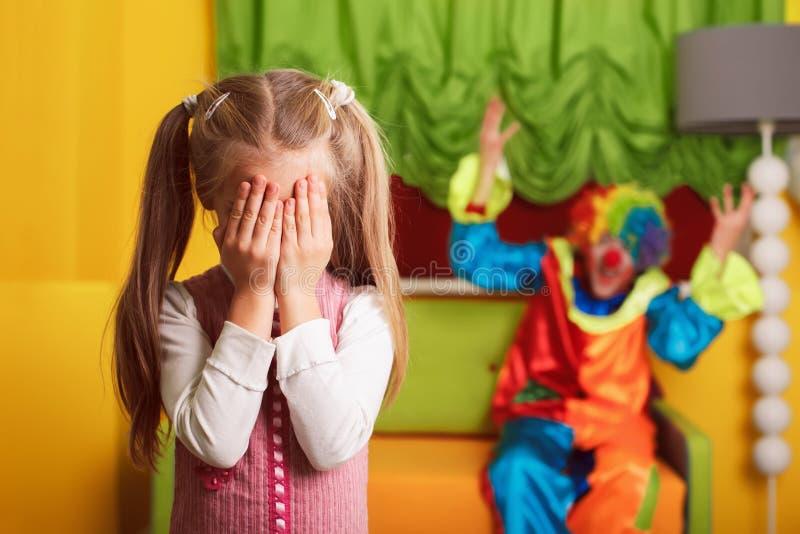 Meisje het spelen de huid - en - zoekt met een vrolijke clown stock afbeelding