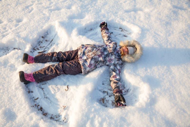 Meisje het spelen in een sneeuw die van de winter genieten royalty-vrije stock afbeeldingen