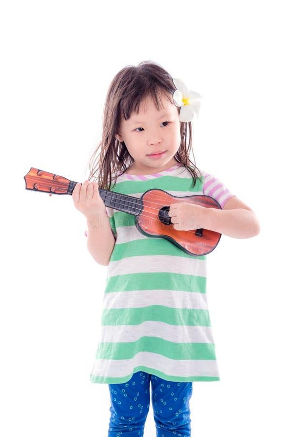 Meisje het spelen gitaarstuk speelgoed over witte achtergrond royalty-vrije stock foto's