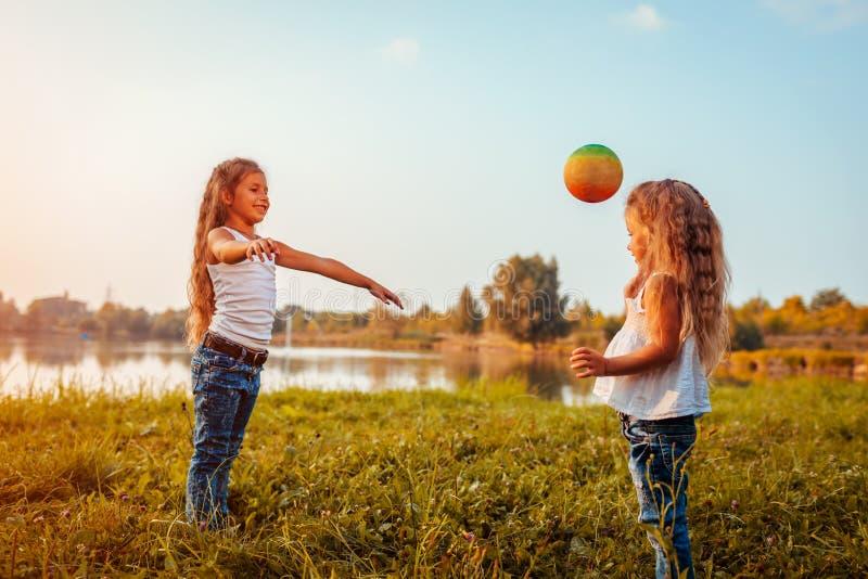 Meisje het spelen met bal met haar zuster in de zomerpark Jonge geitjes die pret hebben in openlucht royalty-vrije stock afbeelding