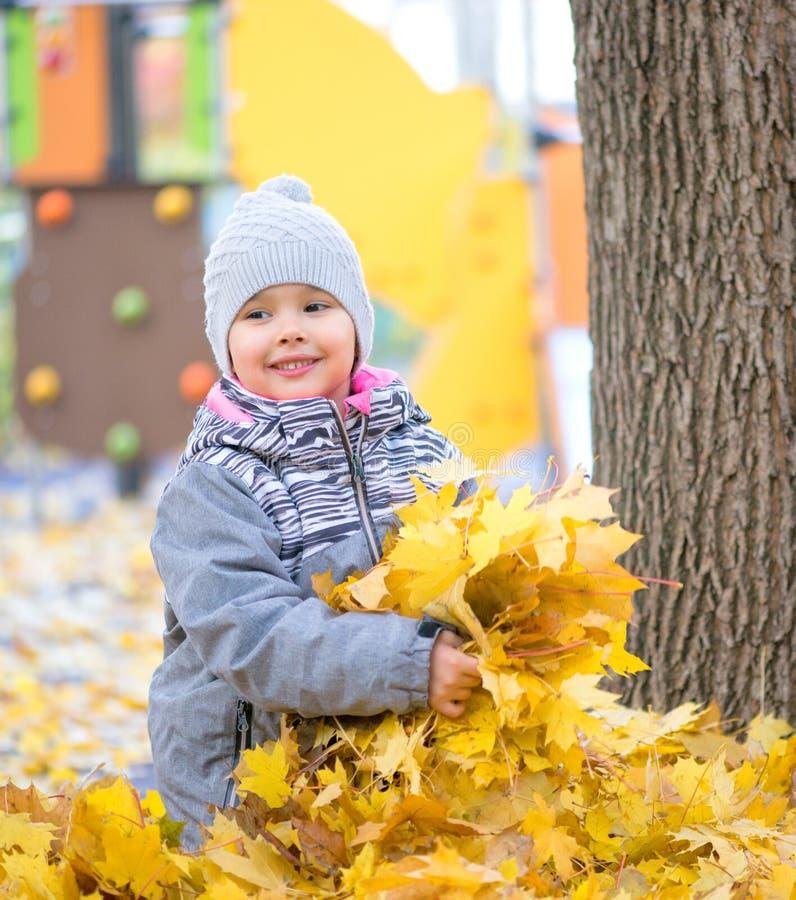 Meisje het spelen met bladeren en het smilling royalty-vrije stock afbeelding