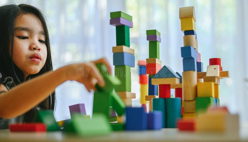 Meisje het spelen met bouwstuk speelgoed blokken die een toren bouwen stock foto