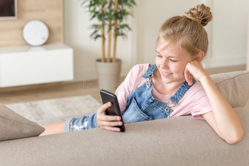 Meisje het spelen met een celtelefoon thuis op een laag stock afbeeldingen