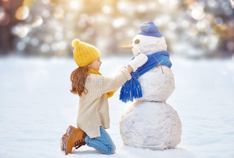 Meisje het spelen met een sneeuwman stock foto's