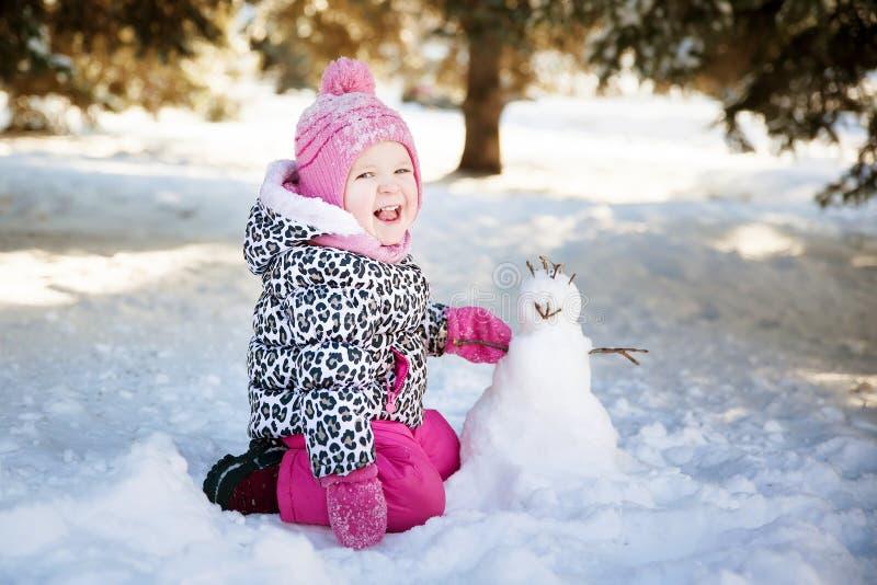 Meisje het spelen met een sneeuwman royalty-vrije stock afbeeldingen
