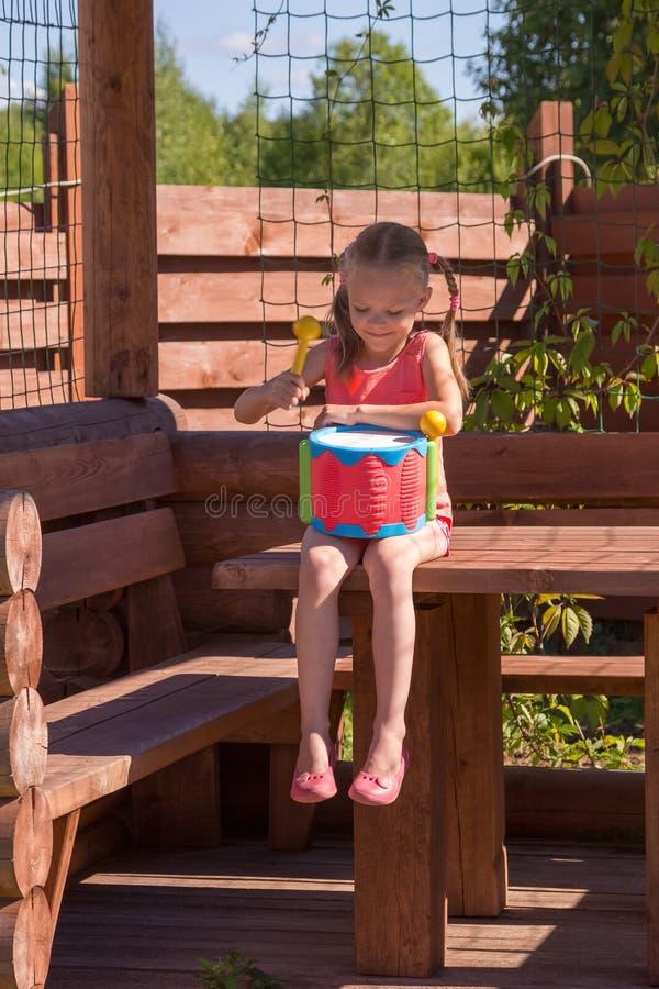 Meisje het spelen met een trommel in houten as stock foto