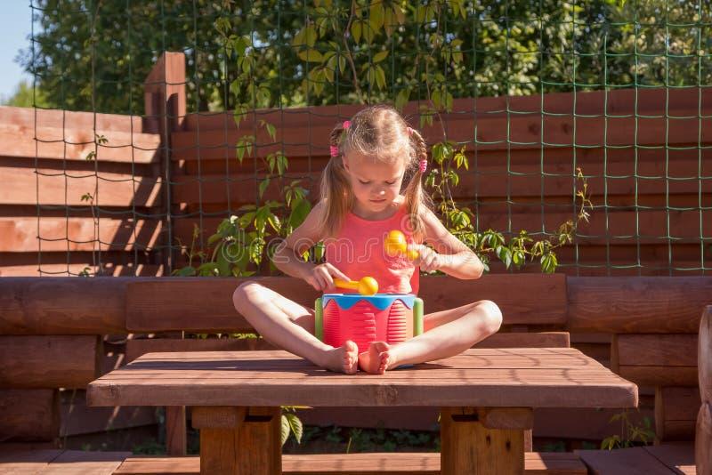 Meisje het spelen met een trommel in houten as royalty-vrije stock foto