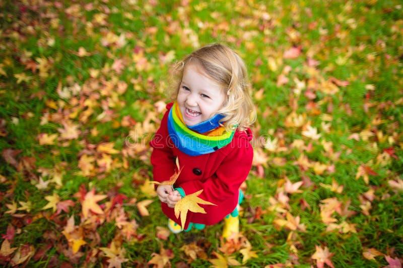 Meisje het spelen met esdoornblad in de herfst stock afbeelding