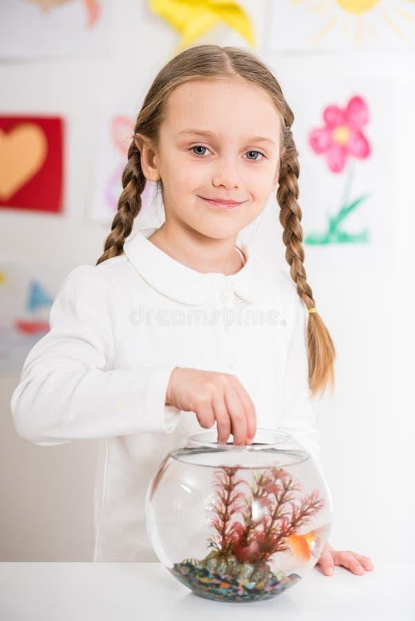 Meisje het spelen met gouden vissen stock afbeelding