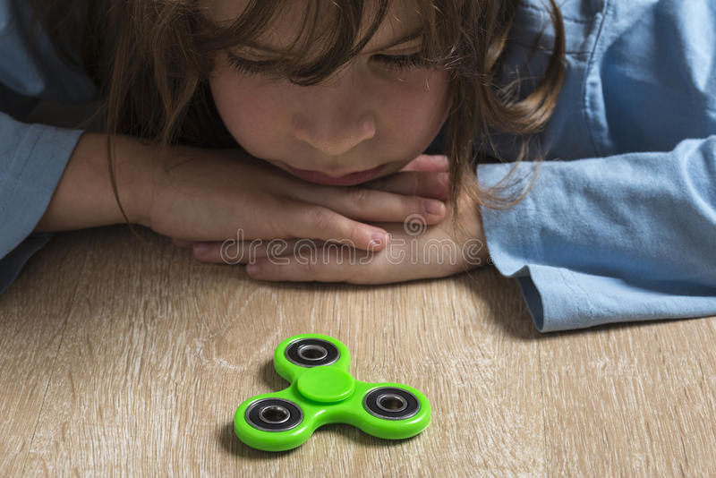 Meisje het spelen met groen friemelt spinnerstuk speelgoed stock afbeeldingen