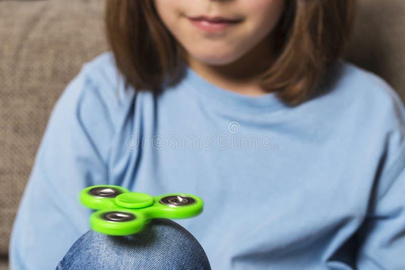 Meisje het spelen met groen friemelt spinnerstuk speelgoed stock fotografie