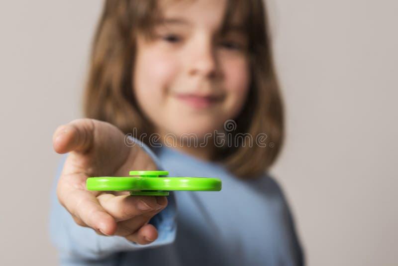 Meisje het spelen met groen friemelt spinnerstuk speelgoed royalty-vrije stock foto