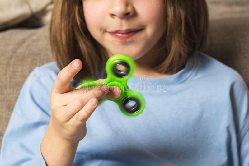 Meisje het spelen met groen friemelt spinnerstuk speelgoed stock foto's