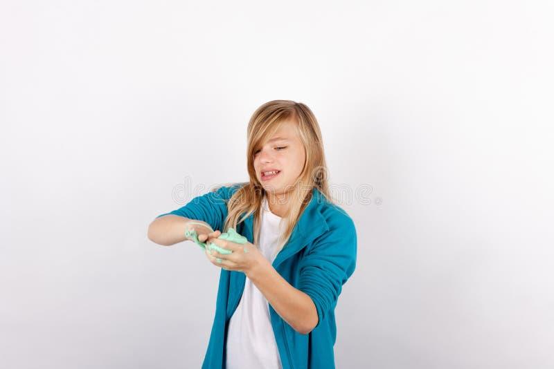 Meisje het spelen met groen slijm kijkt als gunk stock foto's