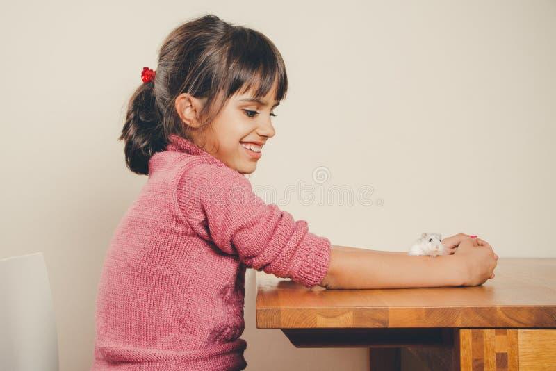 Meisje het spelen met haar hamster stock afbeelding
