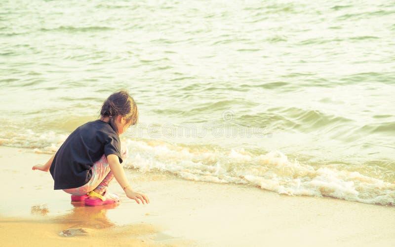 Meisje het spelen met oceaangolf op het strand royalty-vrije stock afbeelding