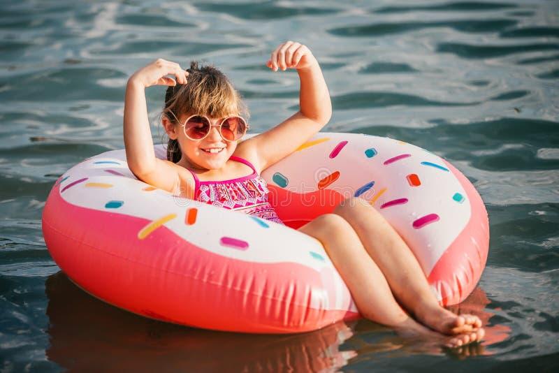 Meisje het spelen met opblaasbare ring in water royalty-vrije stock afbeelding