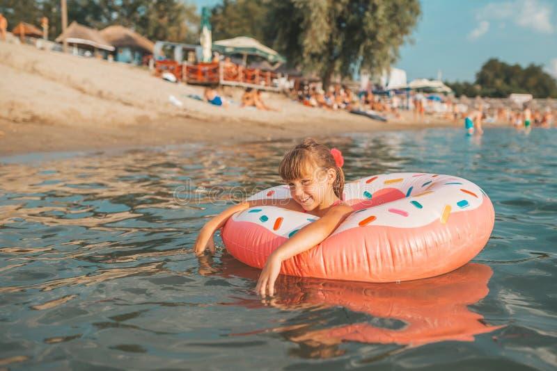 Meisje het spelen met opblaasbare ring in water stock foto