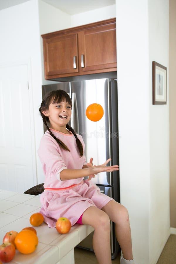 Meisje het spelen met sinaasappelen in keuken royalty-vrije stock foto