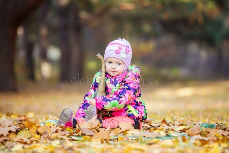 Meisje het spelen met stuk speelgoed dinosaurus in openlucht stock fotografie