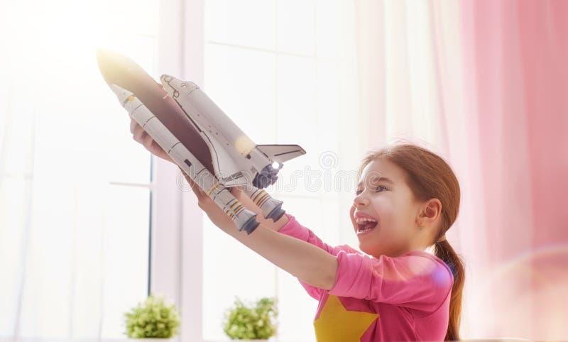 Meisje het spelen met stuk speelgoed raket stock foto