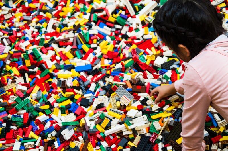 Meisje het spelen met vele plastic delen van de bouwbakstenen stock foto