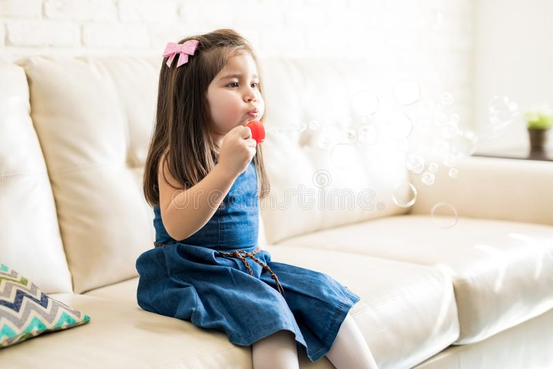 Meisje het spelen met zeepbels thuis stock foto's