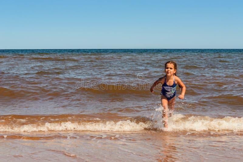 Meisje het spelen op het Cavendish-strand stock afbeeldingen