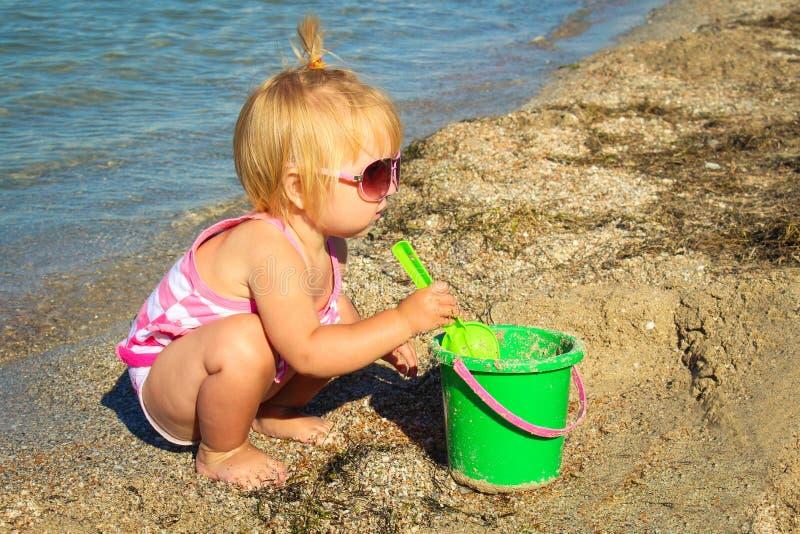 Meisje het spelen op het strand met emmer en schop royalty-vrije stock afbeeldingen