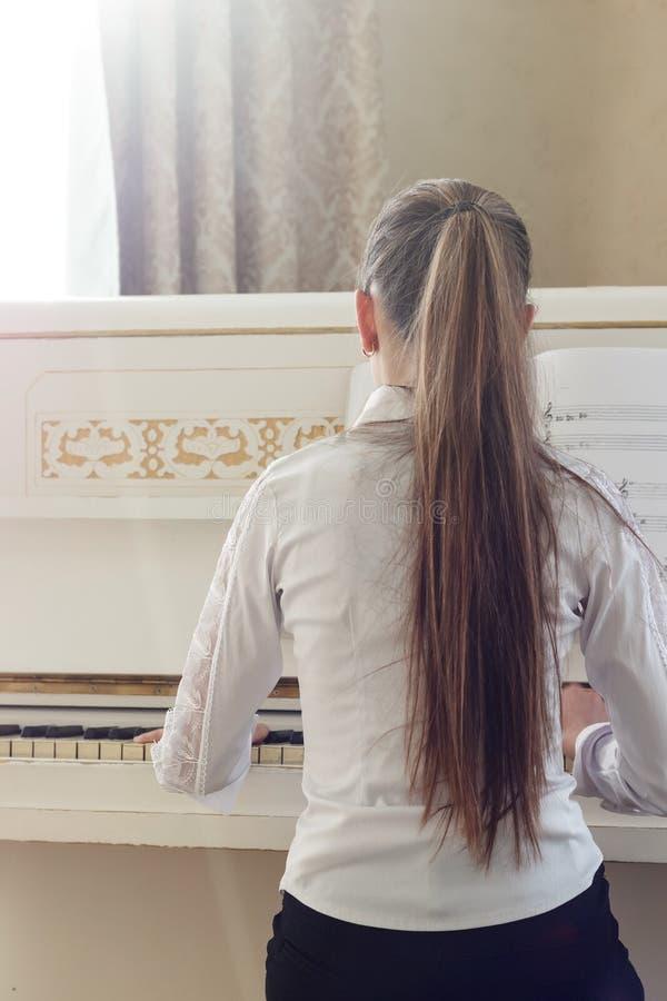 Meisje het spelen op witte piano Een mening van de rug van meisjessi royalty-vrije stock afbeeldingen