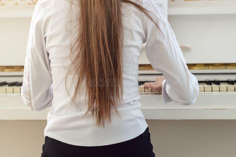 Meisje het spelen op witte piano Een mening van de rug van meisjessi stock foto's