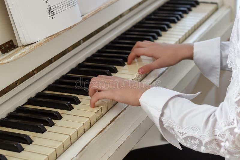 Meisje het spelen op witte piano Handen van sleutels van een meisjes de dringende piano royalty-vrije stock fotografie
