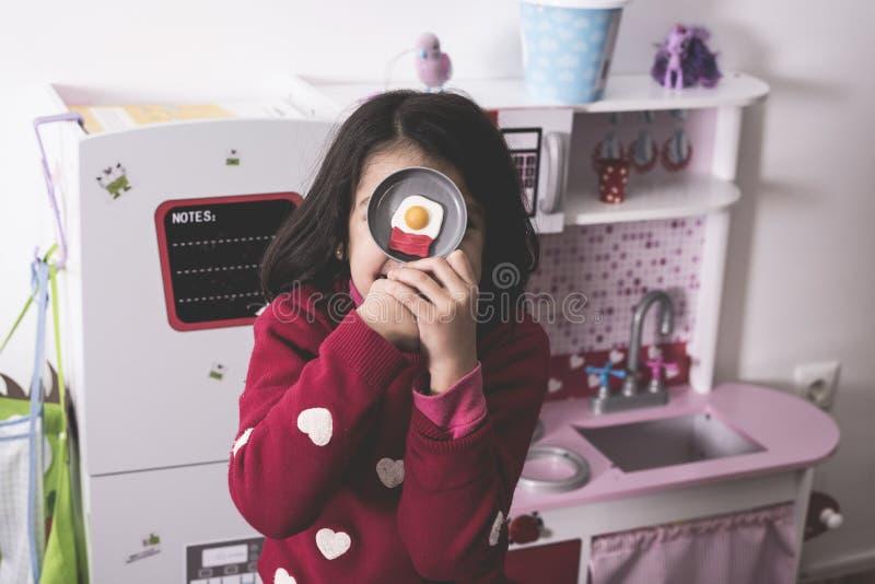 Meisje het spelen in stuk speelgoed keuken met vals gebraden ei stock afbeeldingen