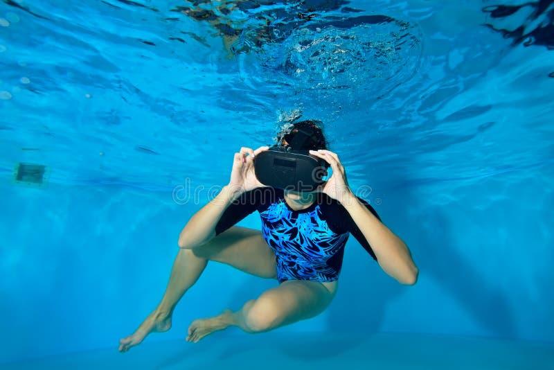 Meisje het spelen videospelletjes onderwater in de pool in een virtuele werkelijkheidshelm op zijn hoofd Virtuele Werkelijkheidss royalty-vrije stock foto's