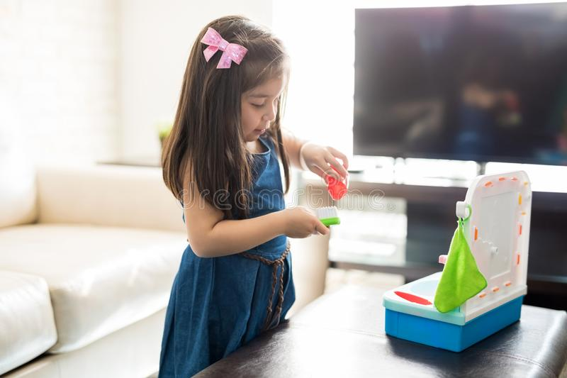 Meisje het spelen in woonkamer met tand het schoonmaken stuk speelgoed reeks stock foto