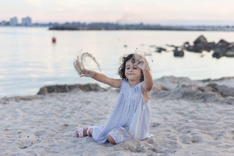 Meisje het spelen in het zand bij schemer royalty-vrije stock afbeeldingen