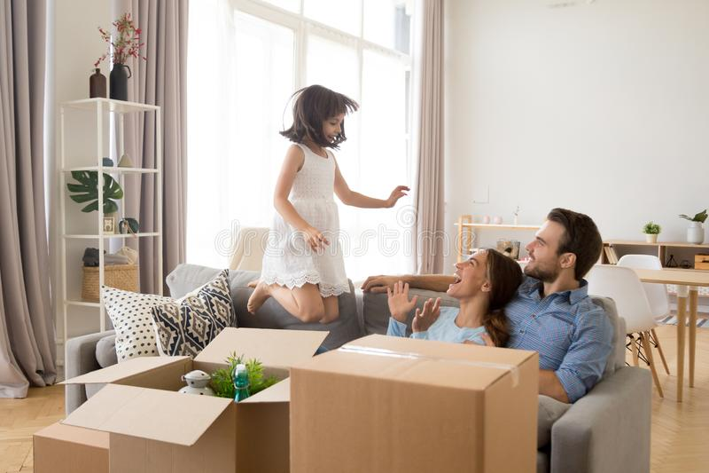 Meisje het springen op laag heeft pret thuis met ouders royalty-vrije stock foto