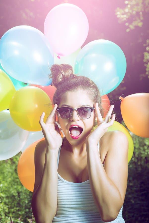 Meisje het stellen met ballons in aard stock fotografie