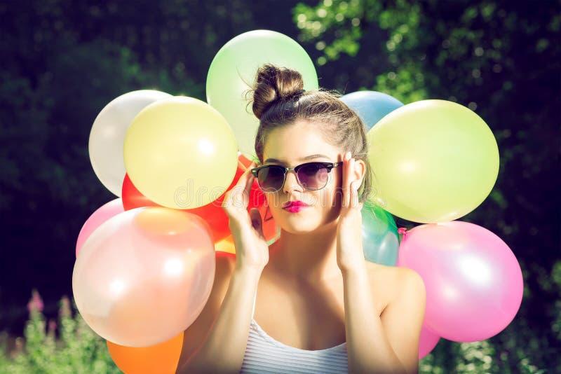 Meisje het stellen met ballons in aard stock foto's