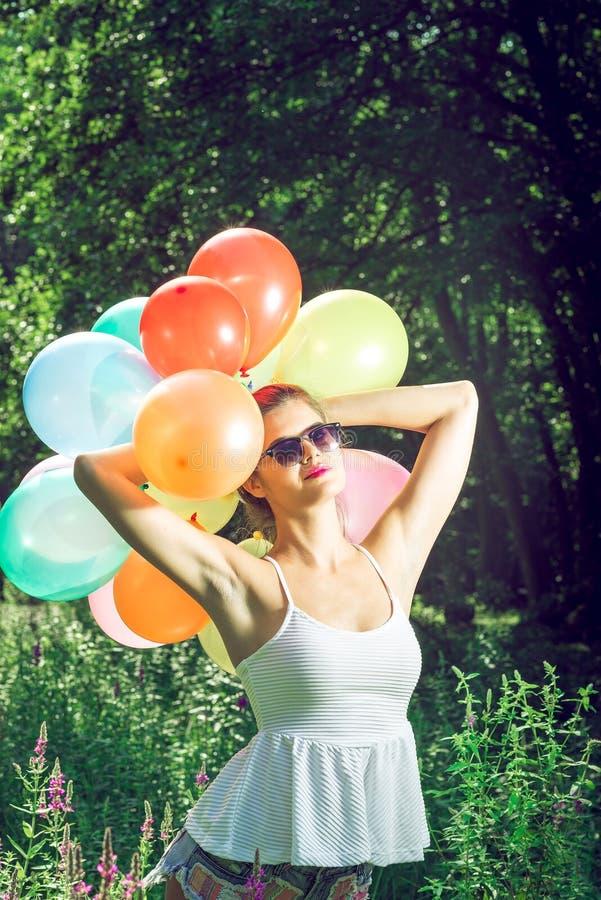 Meisje het stellen met ballons in aard stock foto