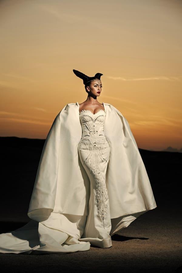 Meisje het stellen op de hemel van de woestijnzonsondergang Vrouw in witte huwelijkskleding en toga stock fotografie