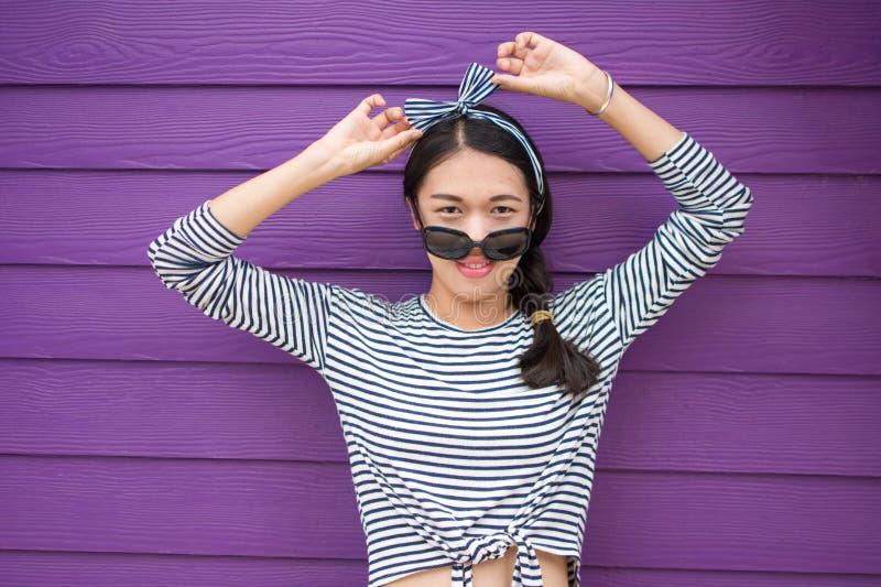 Meisje het stellen tegen kleurrijke houten achtergrond stock afbeelding