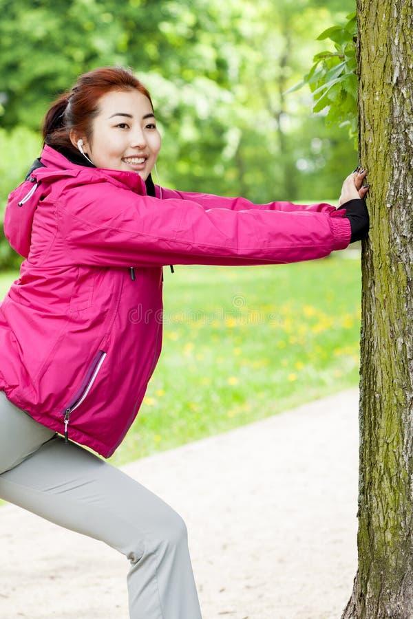 Meisje het uitrekken zich naast boom stock afbeelding