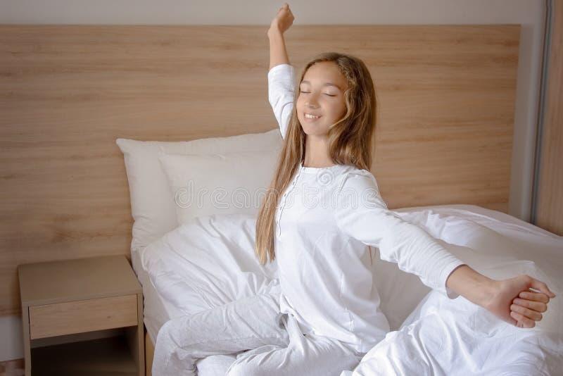 Meisje het uitrekken zich op het bed na kielzog omhoog stock afbeelding