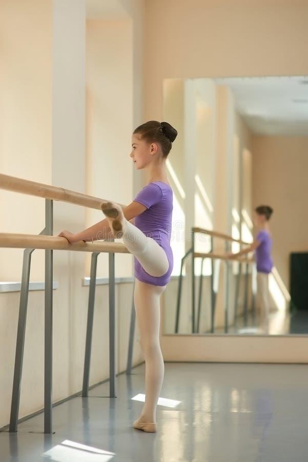 Meisje het uitrekken zich uit in balletstudio stock afbeeldingen