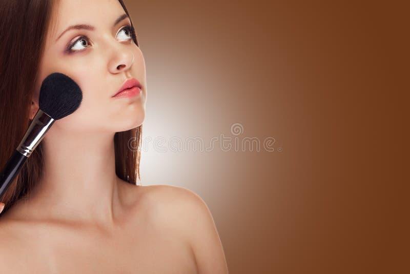 Meisje het van toepassing zijn maakt omhoog met borstel op bruine achtergrond royalty-vrije stock foto's