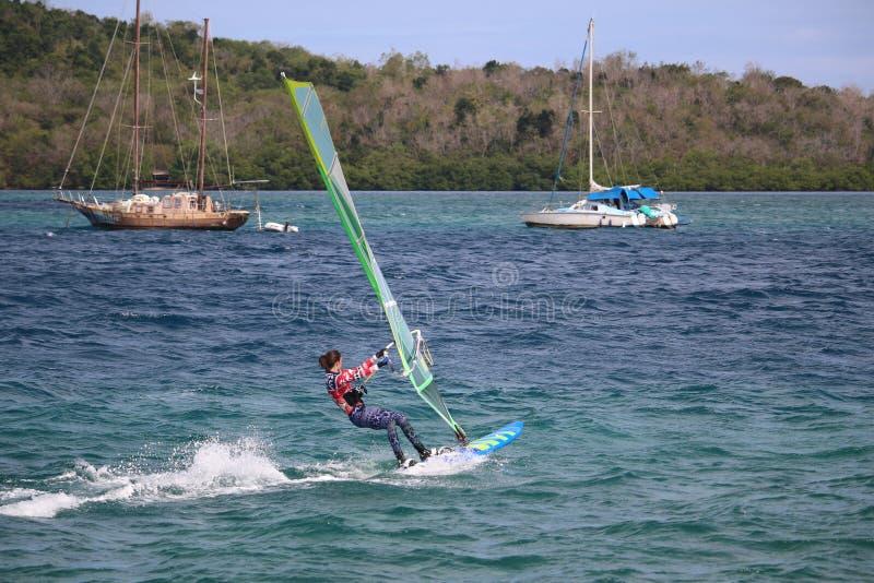 Meisje het windsurfing in Martinique met varende boten in achtergrond/Trois Ilets, Martinique royalty-vrije stock afbeelding