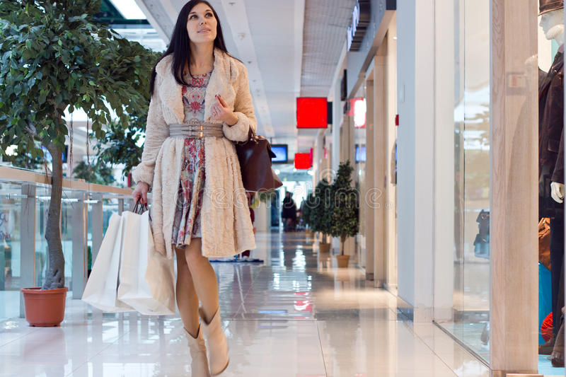 Meisje in het winkelende centrum met het winkelen zakken stock afbeelding