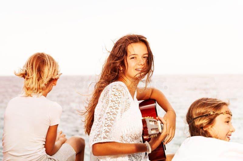 Meisje het zingen met gitaar voor vrienden op het strand stock afbeelding