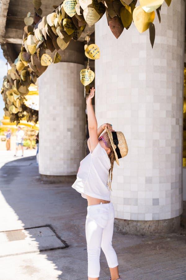 Meisje het zoeken wenst op Gouden die Bodhi dit op een metaalstaaf onder de boom wordt gehangen Sluit van het goud kleurde omhoog stock foto
